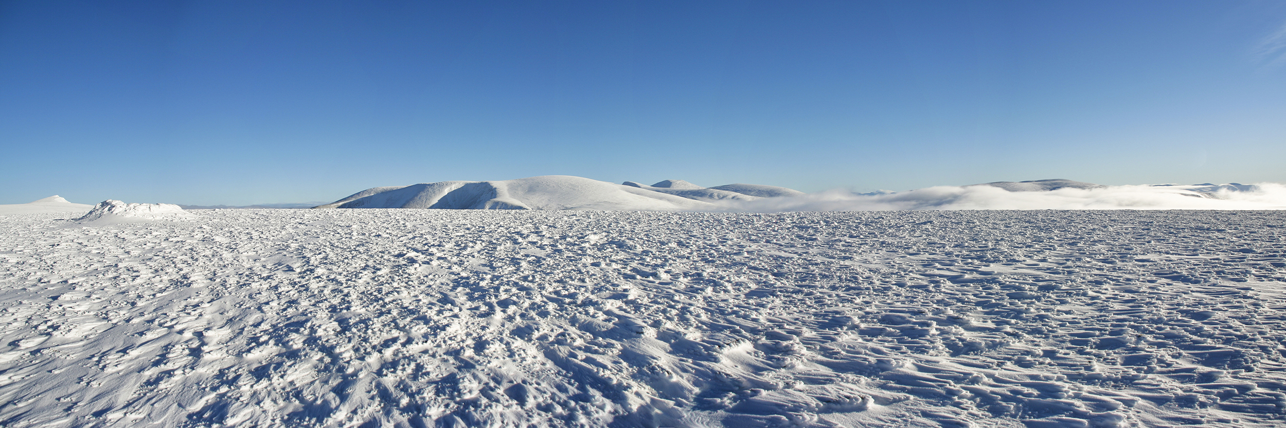 Winter panorama on Sgor Gaoith and distant Braeriach from Carn Ban Mor